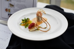 """Fish starter dish - fillet of striped bass with lemon crust, leek confit, tomato jam, slow-poached bass """"pressed roulade"""" with dill-seasoned shrimp, brandied shrimp sauce, celery leaves, chervil, orange and arugula with pickled shallots and pâte à choux cracker."""